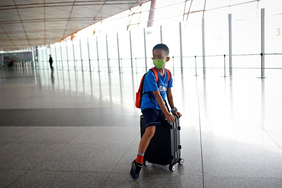 A boy wearing a face mask sits on a suitcase at Beijing's international airport on June 17, 2020. - Beijing's airports cancelled more than 1,200 flights and schools in the Chinese capital were closed again on June 17 as authorities rushed to contain a new coronavirus outbreak linked to a wholesale food market. (Photo by STR / AFP) (Photo by STR/AFP via Getty Images)