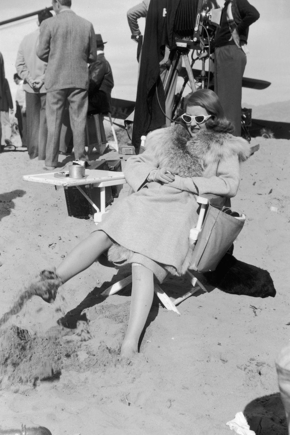 <p> Bette Davis sinks her feet into the sand as she takes a break while filming a scene in Death Valley, California for <em>The Bridge Came C.O.D. </em>in 1941. The actress wasn't exactly dressed appropriately for the beach in her fur-trimmed jacket.</p>