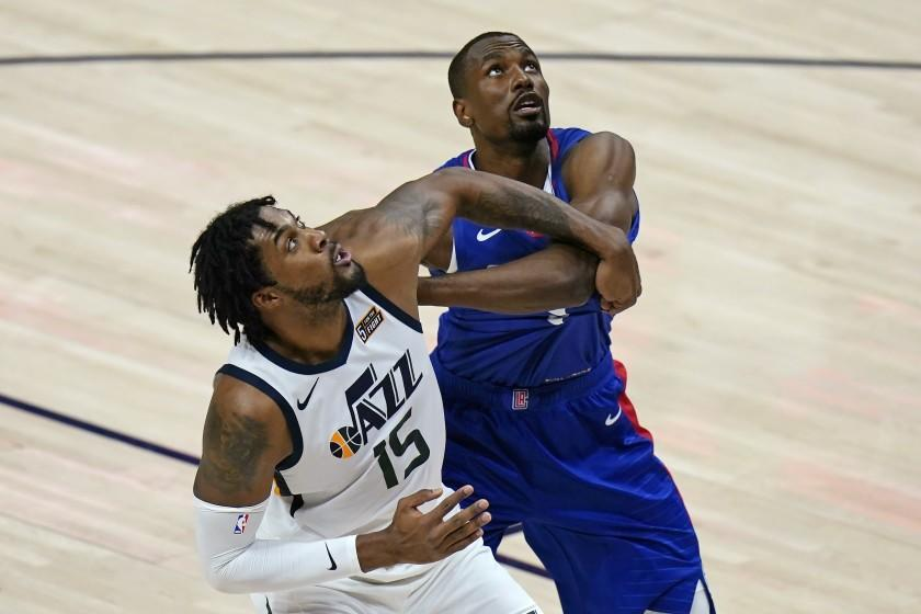 Utah Jazz center Derrick Favors (15) and Los Angeles Clippers forward Serge Ibaka wait for a rebound during the first half of an NBA basketball game Friday, Jan. 1, 2021, in Salt Lake City. (AP Photo/Rick Bowmer)