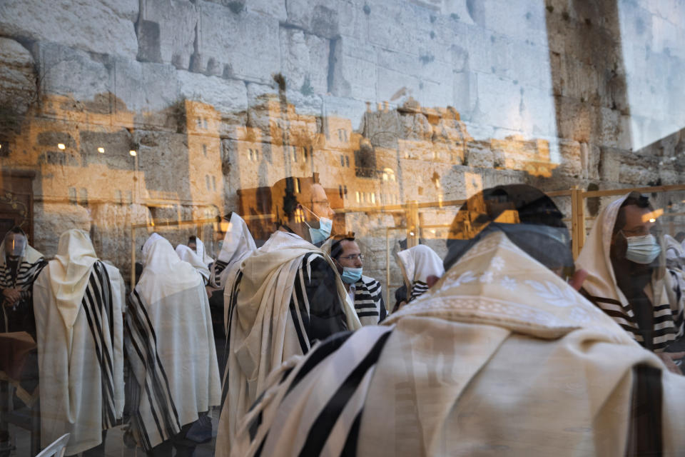 Ultra-Orthodox Jewish men pray in a divided section during nationwide lockdown due to the coronavirus pandemic at the Western Wall, the holiest site where Jews can pray in Jerusalem's old city, Monday, Jan. 11, 2021. (AP Photo/Oded Balilty)