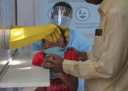 An adult helps hold a child as his nasal swab sample is taken by a health worker at a COVID-19 testing center in Hyderabad, India, Saturday, Oct. 3, 2020. India has crossed 100,000 confirmed COVID-19 deaths on Saturday, putting the country's toll at nearly 10% of the global fatalities and behind only the United States and Brazil. (AP Photo/Mahesh Kumar A.)