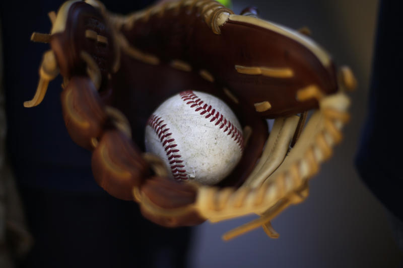 Peyton Berroth carries a baseball in his glove as he arrives to Petco Stadium before an opening day baseball game between the Los Angeles Dodgers and the San Diego Padres on Sunday, March 30, 2014, in San Diego. (AP Photo/Gregory Bull)