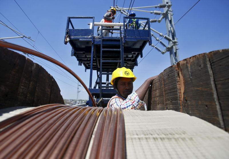 A DMRC worker installs copper wires at the construction site of Ajronda station, outskirts of New Delhi
