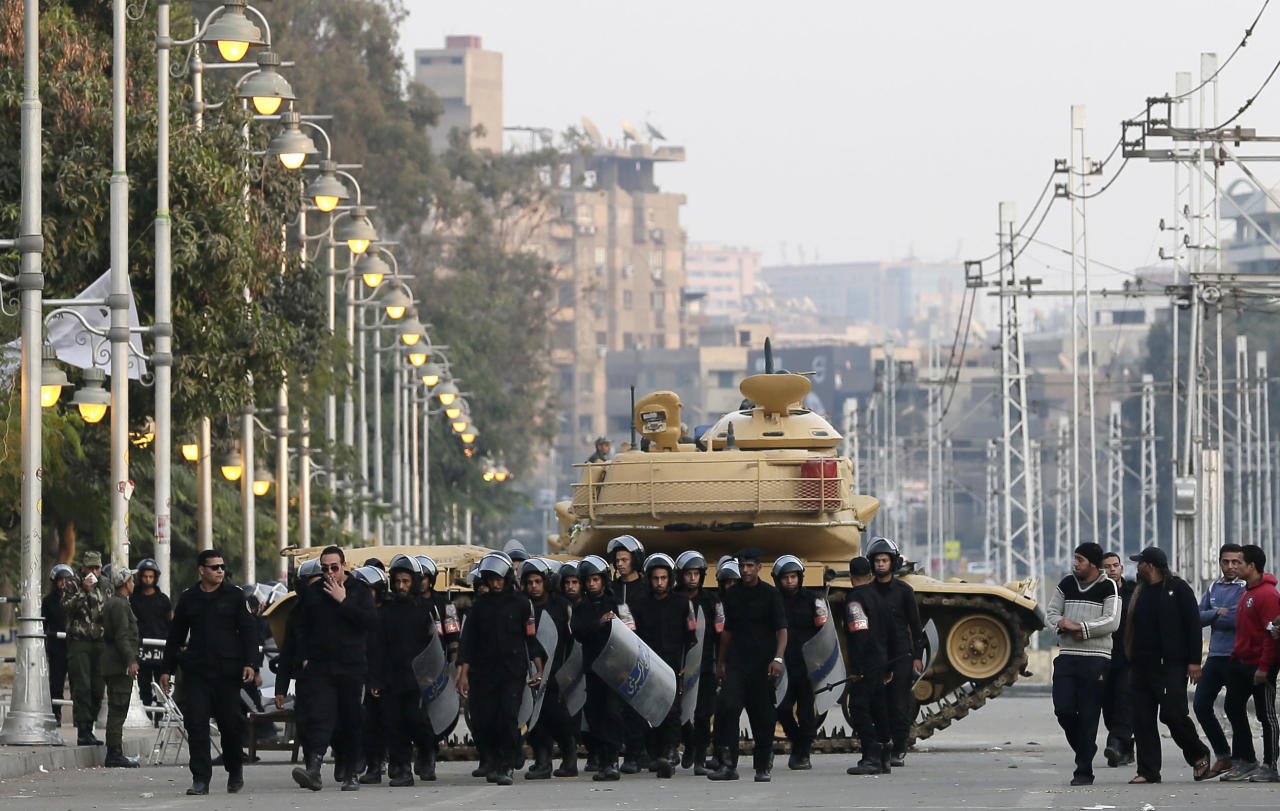 "Egyptian riot police walk past a military tank guarding the presidential palace in Cairo, Egypt, Sunday, Dec. 16, 2012. Key Egyptian rights groups called Sunday for a repeat of the first round of the constitutional referendum, alleging the vote was marred by widespread violations. Islamists who back the disputed charter claimed they were in the lead with a majority of ""yes"" votes. (AP Photo/Hassan Ammar)"