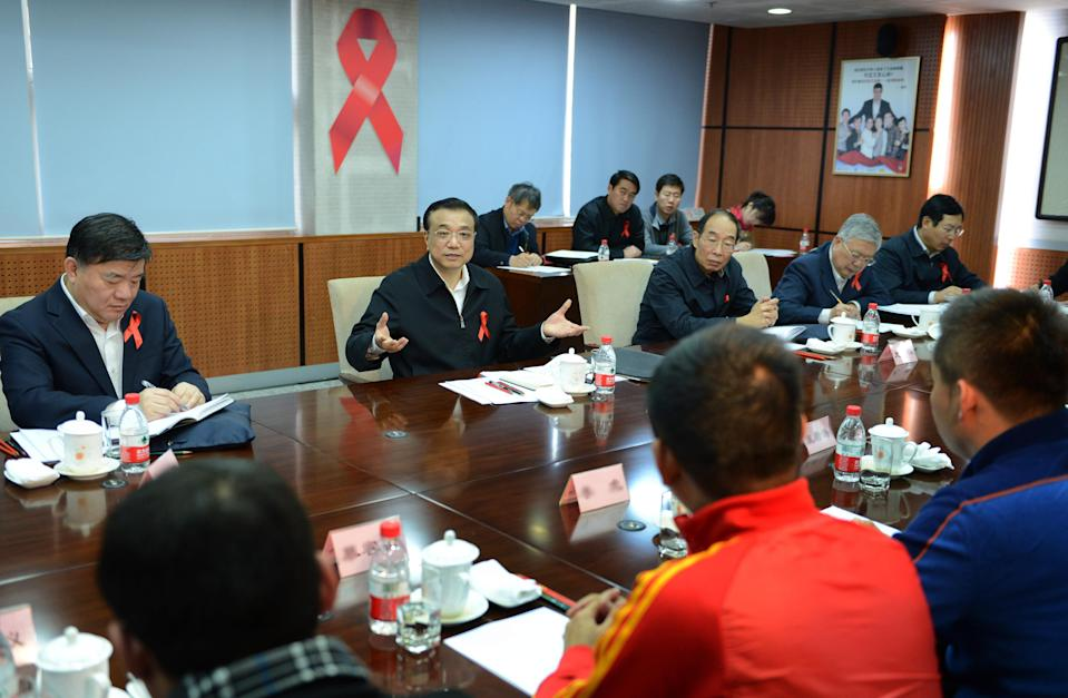 In this photo released by China's Xinhua News Agency, taken on Monday, Nov. 26, 2012, Chinese Vice Premier Li Keqiang, back center, speaks at a symposium attended by representatives of HIV/AIDS related non-governmental organizations and international organizations in Beijing, China. During the meeting Monday Li said health facilities that discriminate against people with HIV would be severely punished. (AP Photo/Xinhua, Ma Zhancheng) NO SALES