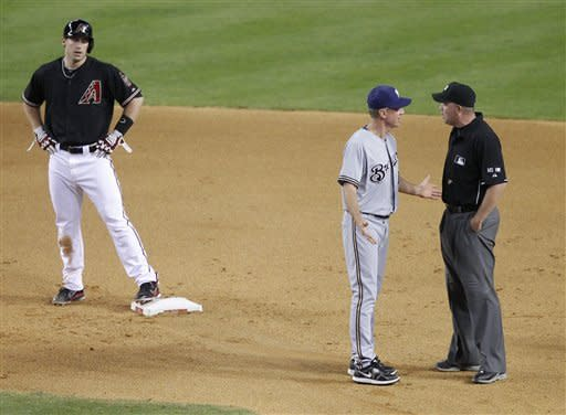 Milwaukee Brewers manager Ron Roenicke argues with umpire Ron Kulpa, right, as Arizona Diamondbacks' Paul Goldschmidt stands on second during the fourth inning of a baseball game, Saturday, May 26, 2012, in Phoenix. Roenicke was arguing the ruling that Goldschmidt was safe with a double after a late tag by Brewers' Rickie Weeks. (AP Photo/Matt York)