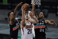 Phoenix Suns forward Dario Saric (20) drives to the basket against San Antonio Spurs forward Rudy Gay (22) and guard Devin Vassell (24) during the first half of an NBA basketball game in San Antonio, Sunday, May 16, 2021. (AP Photo/Eric Gay)