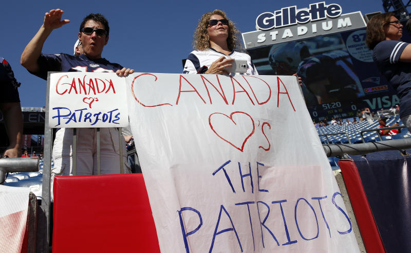 New England Patriots fans hold signs referring to Canada before an NFL football game between the Patriots and the Houston Texans. (AP)