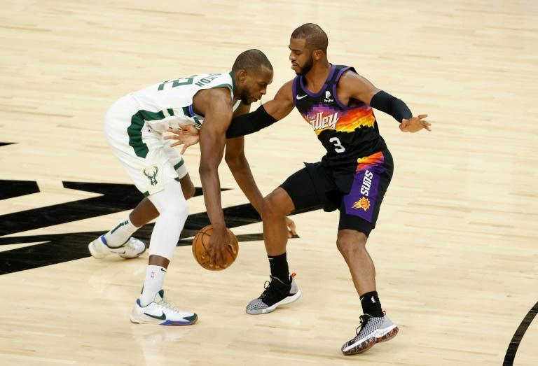 Milwaukee's Khris Middleton, left, drives against Phoenix's Chris Paul in a regular-season meeting between the two teams that will meet in the NBA Finals starting Tuesday