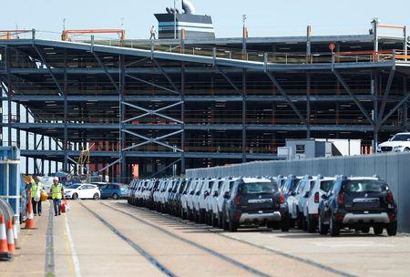 sCars readied for export are parked next to a vehicle storage facility on the dockside at the ABP port in Southampton