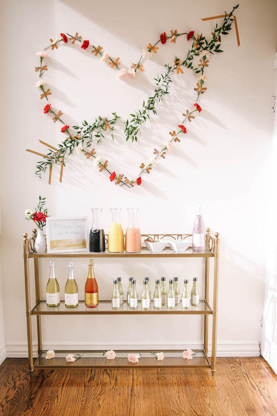 """<p>There's nothing a few rose petals can't make better. <a href=""""https://www.housebeautiful.com/lifestyle/gardening/g13074130/beautiful-flower-images/"""" rel=""""nofollow noopener"""" target=""""_blank"""" data-ylk=""""slk:Fresh flowers"""" class=""""link rapid-noclick-resp"""">Fresh flowers</a>, on and off your bar cart or buffet table, add a romantic touch to any brunch. This heart display is seriously Insta-worthy.</p><p>Get the tutorial at <a href=""""http://theeverygirl.com/how-to-host-a-galentines-day-brunch/"""" rel=""""nofollow noopener"""" target=""""_blank"""" data-ylk=""""slk:The Every Girl"""" class=""""link rapid-noclick-resp"""">The Every Girl</a>.</p>"""