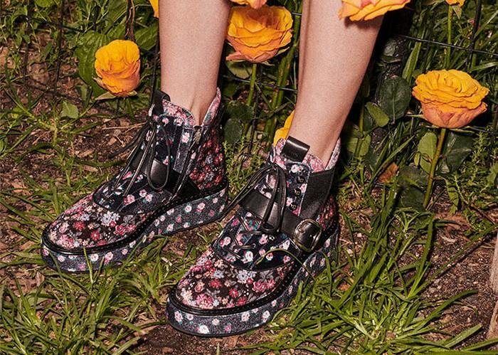 Someone standing in a garden wearing a pair of Coach leather boots, shown in black with pink floral print.