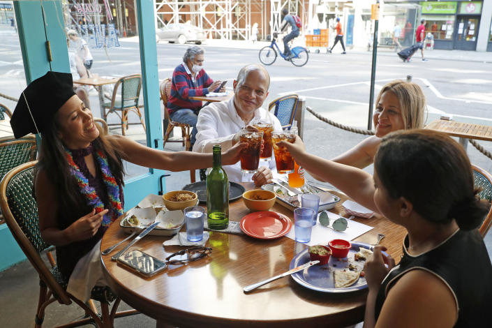 A graduate toasts with her family at a restaurant on Manhattan's Upper West Side on July 20, 2020. (AP Photo/Kathy Willens, File)