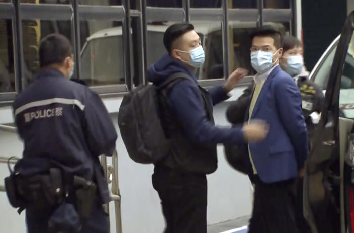 In this image taken from a video, former legislator and District Council member Gary Fan, right, is arrested by police officers at a police station in Hong Kong, Wednesday, Jan. 6, 2021. Hong Kong police arrested about 50 pro-democracy figures Wednesday for allegedly violating the new national security law by participating in an unofficial primary election last year held to increase their chances of controlling the legislature, according to political parties and local media. (TVB via AP)