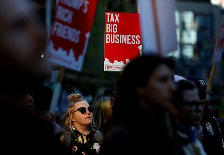 FLE PHOTO: A woman holds a sign supporting the taxation of big businesses during a protest in front of the Amazon Spheres to demand that the city of Seattle tax the largest corporations to help fund affordable housing, according to organizers, in Seattle, Washington, U.S., April 10, 2018.  REUTERS/Lindsey Wasson/File Photo