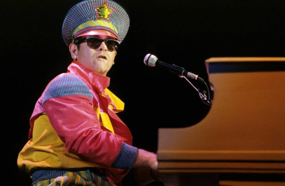 <p>Back in 1982, Elton John kept with the decade's trend in a bright, colorful ensemble. (Photo: Getty Images) </p>