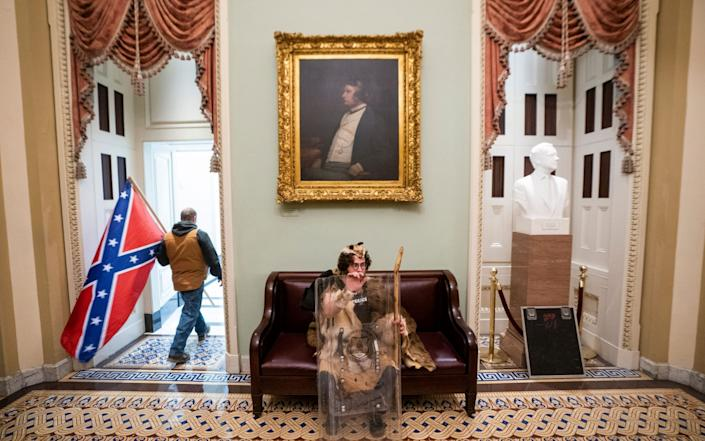 Protesters carrying Confederate flags entered the Capitol on Wednesday - EPA