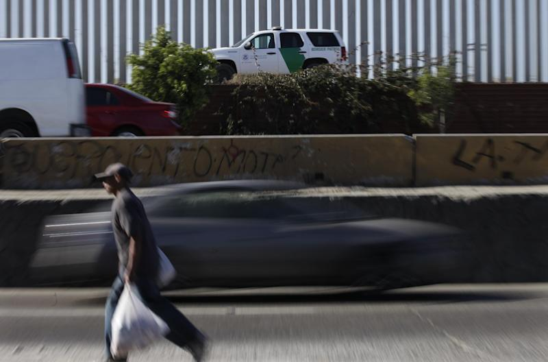 A Border Patrol agent drives his white and green vehicle, above, along the border fence as cars and people cross a road the runs alongside the international border in Tijuana, Mexico,  Friday, June 22, 2012. Former Border Patrol agents Raul Villarreal and his older brother and fellow former agent, Fidel Villarreal, are charged with smuggling hundreds of Brazilians and Mexicans to the United States in Border Patrol vehicles. Federal prosecutors say the brothers were tipped they were under investigation in June 2006, prompting them to empty their retirement accounts and flee to Mexico. (AP Photo/Gregory Bull)