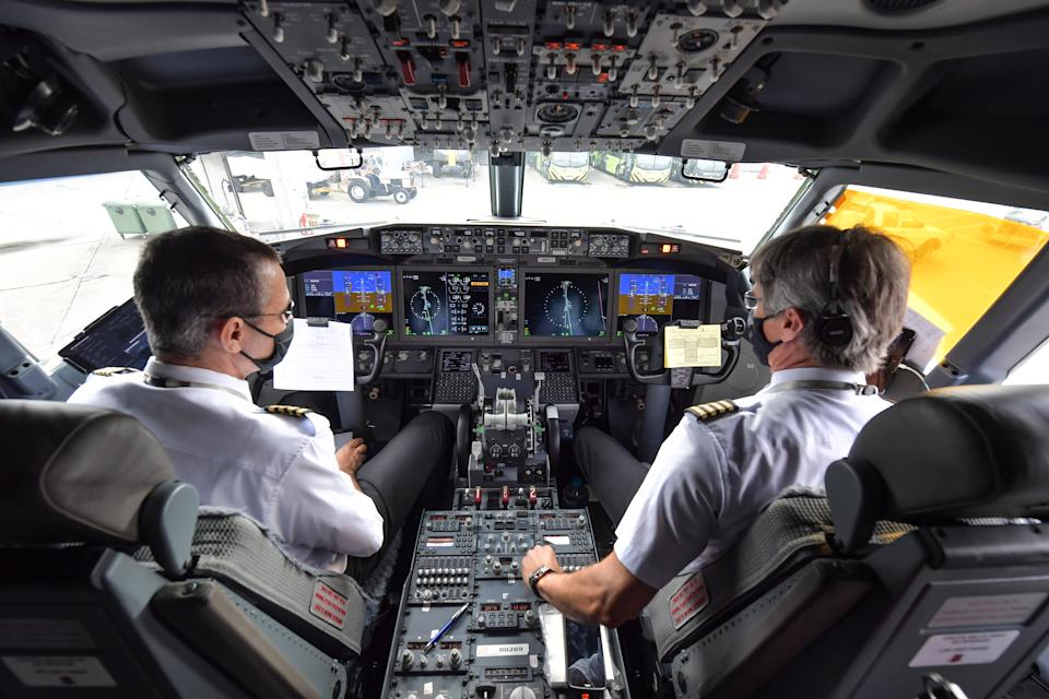 Pilots are pictured in the cockpit of a Boeing 737 MAX aircraft operated by low-cost airline Gol as it sits on the tarmac before take off at Guarulhos International Airport, near Sao Paulo on December 9, 2020, as the 737 MAX returns into use more than 20 months after it was grounded following two deadly crashes. (Photo by NELSON ALMEIDA / AFP) (Photo by NELSON ALMEIDA/AFP via Getty Images)