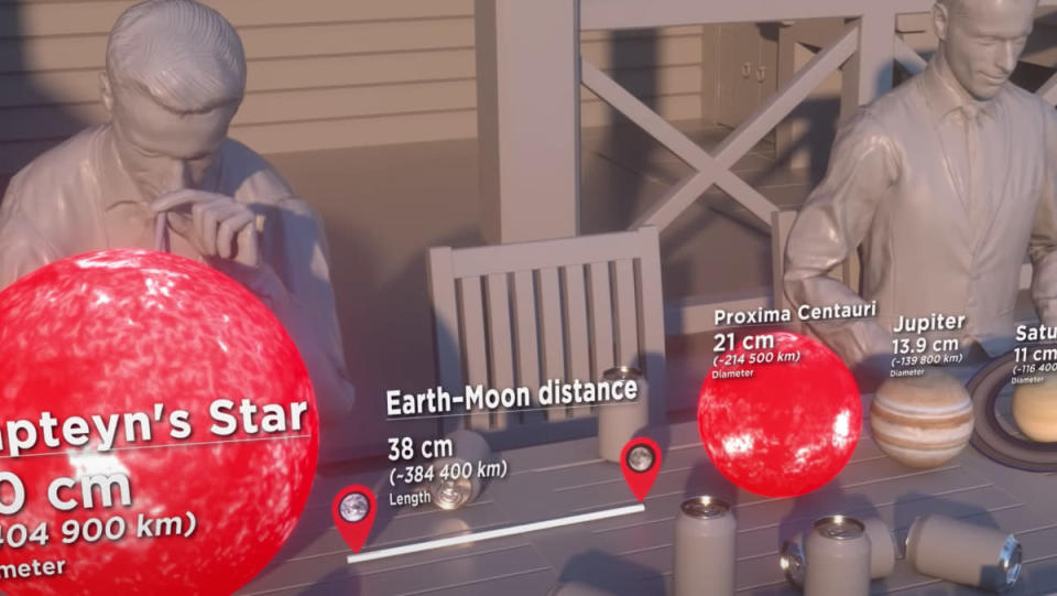 An animation of human-scale planets and stars in front of two people sitting behind a table.