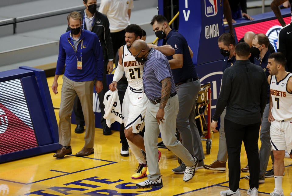 Denver Nuggets star Jamal Murray limps off the floor after tearing his left ACL against the Golden State Warriors on Monday night. (Ezra Shaw/Getty Images)