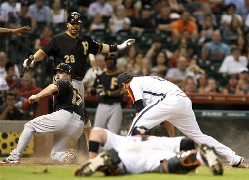 Pittsburgh Pirates runner Drew Sutton (17) is safe after running home after a wild pitch to Rod Barajas (26) as the Houston Astros players scramble for the ball during the ninth inning of a baseball game, Friday, July 27, 2012, in Houston. (AP Photo/Eric Kayne)