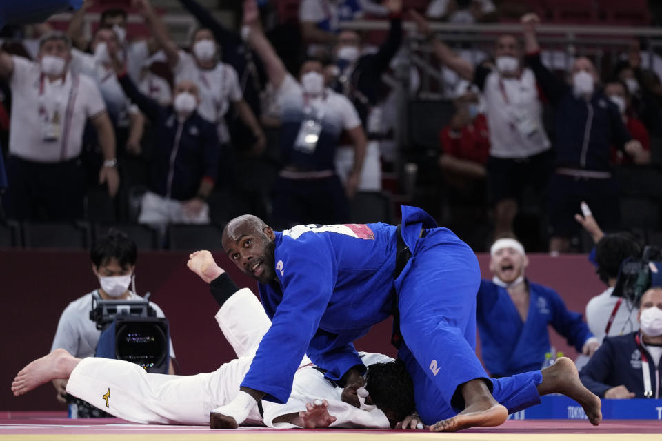 Teddy Riner of France, top, reacts while competing against Aaron Wolf of Japan during their gold medal match in team judo competition at the 2020 Summer Olympics, Saturday, July 31, 2021, in Tokyo, Japan. (AP Photo/Vincent Thian)