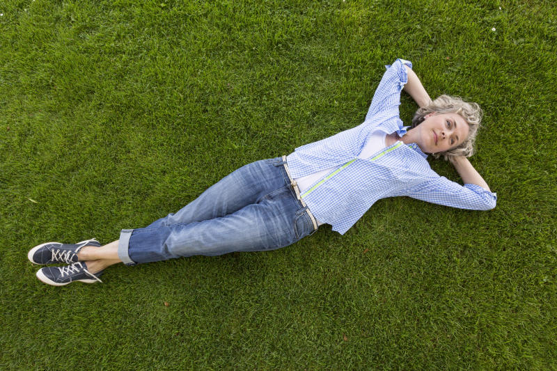 Smiling woman lying down on grass.