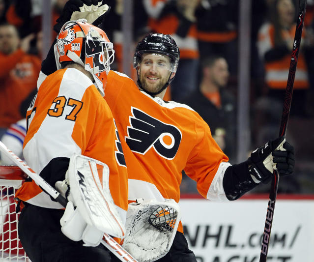 Philadelphia Flyers' Andrew MacDonald, right, congratulates goalie Brian Elliott at the end of an NHL hockey game against the New York Rangers, Saturday, April 7, 2018 in Philadelphia. The Flyers won 5-0. (AP Photo/Tom Mihalek)