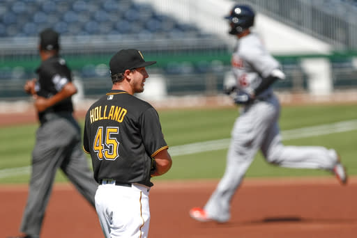 Detroit Tigers' Jeimer Candelario, right, rounds the bases past Pittsburgh Pirates starting pitcher Derek Holland with a home run in the first inning of a baseball game, Saturday, Aug. 8, 2020, in Pittsburgh. (AP Photo/Keith Srakocic)