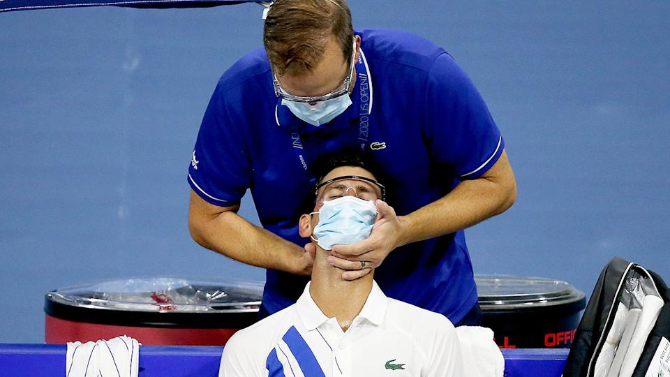 Djokovic is seen in this picture being treated for a neck complaint.