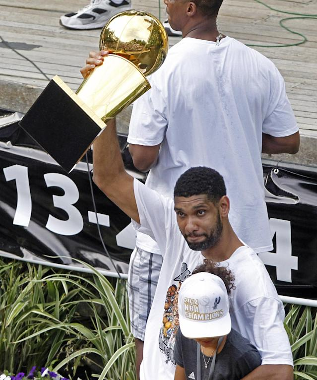 San Antonio's Tim Duncan holds up the trophy during the Spurs' parade and celebration in San Antonio, Texas, Weds., June 18, 2014. (AP Photo/Michael Thomas)