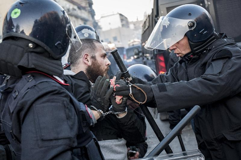 Anti-riot policemen arrest a man during clashes with a group of rioters during a rally against the political meeting of Matteo Salvini, general secretary of far-right party Lega Nord in Naples on March 11, 2017 (AFP Photo/Renato ESPOSITO)