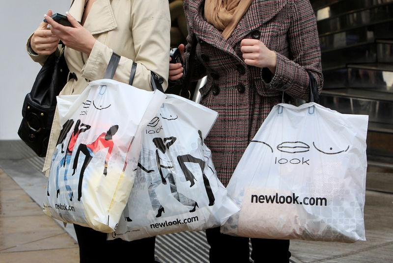 Women hold New Look shopping bags on Oxford Street in London