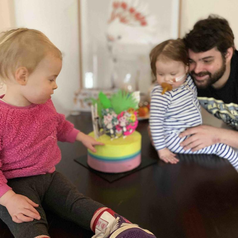 Adrien holds Chloé as she and Nina look at their birthday cake.