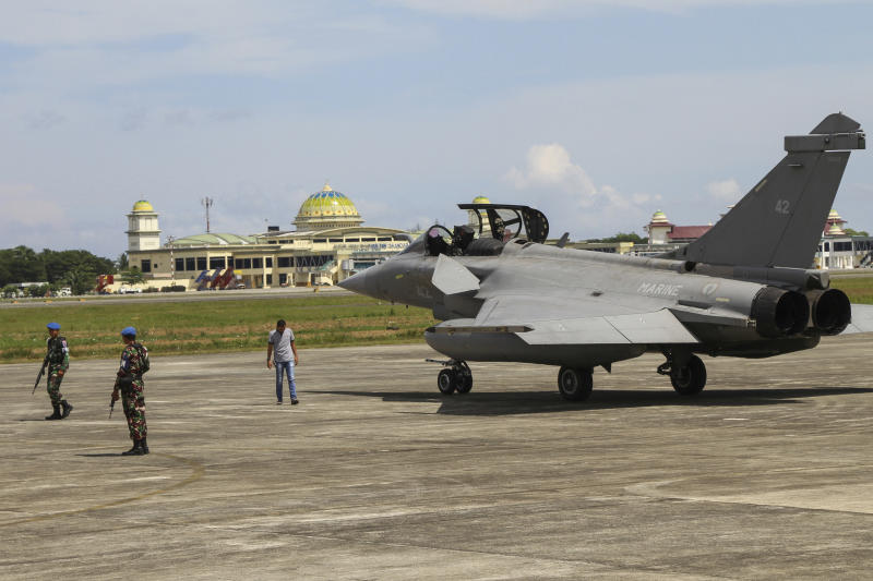 Indonesian military personnel stand guard near one of seven French Navy Rafale jet fighters parked on the tarmac at Sultan Iskandar Muda Air Base in Aceh Besar, Indonesia, Sunday, May 19, 2019. Poor weather has forced the seven fighters from French Navy aircraft carrier Charles de Gaulle taking part in a training exercise to make emergency landings in northern Indonesia. (AP Photo/Khalis Surry)