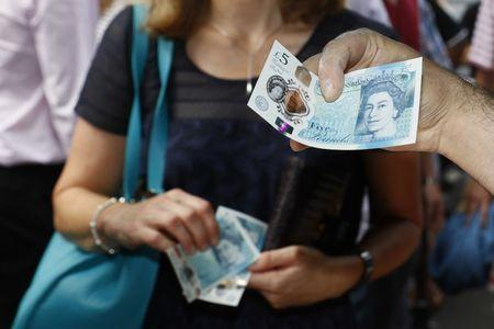 A food seller holds  a new polymer five pound note at Whitecross Street Market in London