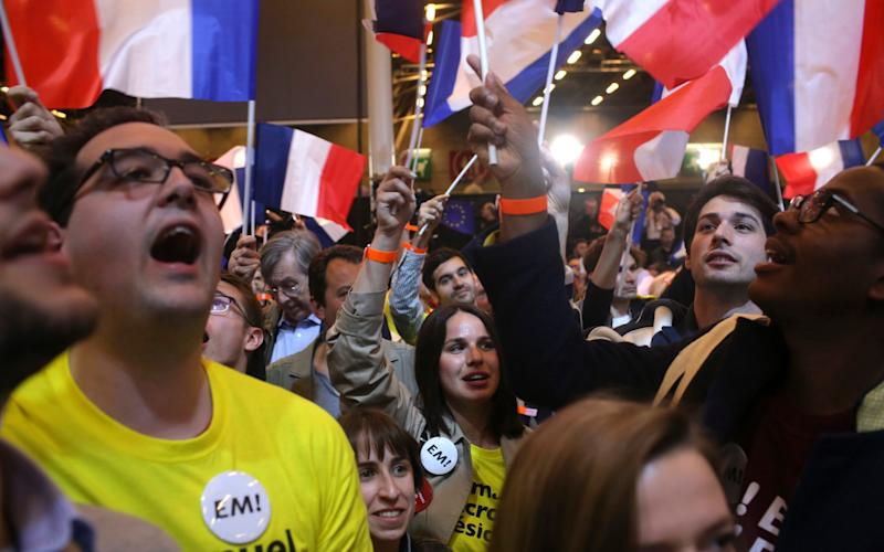 Supporters of French centrist candidate Emmanuel Macron rally at his election day headquarters in Paris - Credit: Thibault Camus/ AP