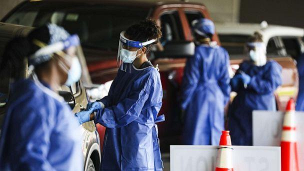 PHOTO: Healthcare workers test people at a Covid-19 testing site in the parking garage for the Mahaffey Theater in St. Petersburg, Fla., July 14, 2020. (Bloomberg via Getty Images)