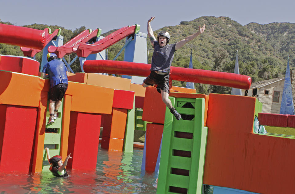 Other contestants compete on a 'Wipeout' course. (Photo by Mike Weaver/Walt Disney Television via Getty Images)