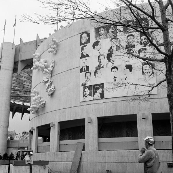 "This April 1964 photo provided by The Andy Warhol Foundation for the Visual Arts, Inc. shows a 20x20 foot mural depicting mug shots of the NYPD's 13 most-wanted criminals by Andy Warhol, mounted on the curved facade of the New York State Pavilion at the 1964 New York World's Fair in the Queens borough of New York. The fair celebrated ""The World of Tomorrow,"" but Warhol may have been ahead of his time. His monumental piece commissioned specifically for the fair was deemed too edgy for the family-friendly event and painted over just before opening day. Now, 50 years later, the work is the focus of a museum exhibition being staged on the very fairgrounds where the pop-art provocateur was infamously censored. (AP Photo/The Andy Warhol Foundation for the Visual Arts, Inc./Artists Rights Society)"
