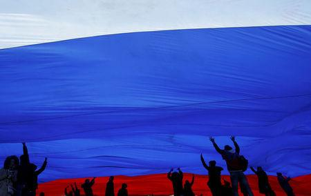 FILE PHOTO: People hold a giant Russian national flag during a festive concert marking the second anniversary of Russia's annexation of the Crimea region, in Red Square in central Moscow, Russia March 18, 2016.  REUTERS/Maxim Shemetov/File Photo
