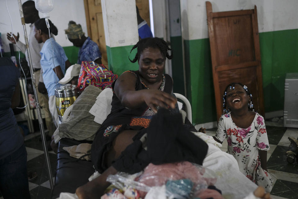 Younaika laughs next to her mother Jertha Ylet who was injured in the 7.2 magnitude earthquake one week prior, at the Immaculate Conception Hospital, also known as the General Hospital of Les Cayes, Haiti, Sunday, Aug. 22, 2021. Her 5-year-old daughter, who was not injured, shares her bed, and they have no home to return to, after the quake brought down their house in Camp-Perrin, killed her father and two other relatives and seriously injured her brother. (AP Photo/Matias Delacroix)