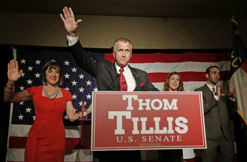 Thom Tillis waves to supporters as he celebrates with his wife Susan, left, son Ryan Tillis, and daughter Lindsay, second from right, at a election night rally in Charlotte, N.C., after winning the Republican nomination for the U.S. Senate Tuesday, May 6, 2014. Tillis, the Republican establishment's favored son in North Carolina, won the state's Senate nomination by running as a proud conservative who's not terribly different from his tea party and Christian-right opponents. (AP Photo/Chuck Burton)