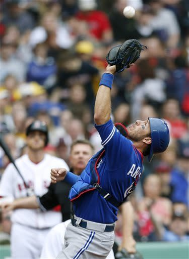 Toronto Blue Jays' J.P. Arencibia makes the catch on a pop foul by Boston Red Sox's Jonny Gomes, background left, during the fourth inning of a baseball game in Boston, Saturday, May 11, 2013. (AP Photo/Michael Dwyer)