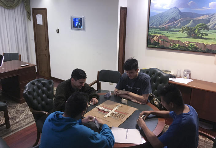 In this Nov. 8, 2019 photo, Venezuelan guardsmen play a game of dominoes inside Panama's Embassy, in Caracas, Venezuela. The group of 16 Venezuela troops holed up for seven months at the foreign embassy after revolting against President Nicolas Maduro said they have managed to flee the country. (AP Photo)