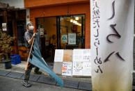 Sixty-year-old Yashiro Haga holds a curtain as he prepares for the opening of his ramen noodle shop 'Shirohachi', amid the coronavirus disease (COVID-19) outbreak, in Tokyo