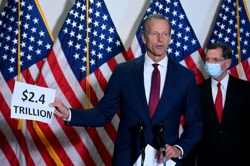 Senator Thune holds a sign while speaking at a news conference at the U.S. Capitol in Washington
