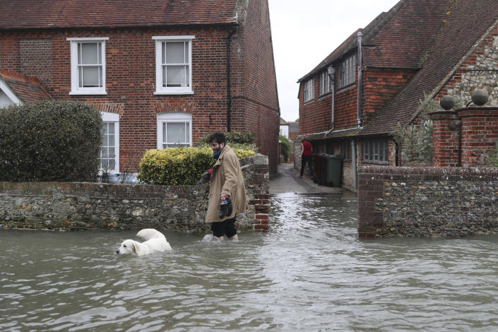 A man walks with a dog in flood water, in the aftermath of Storm Ciara, in Bosham, Sussex , England, Monday Feb. 10, 2020. Storm Ciara battered the U.K. and northern Europe with hurricane-force winds and heavy rains Sunday, halting flights and trains and producing heaving seas that closed down ports. Soccer games, farmers' markets and cultural events were canceled as authorities urged millions of people to stay indoors, away from falling tree branches. (Steve Parsons/PA via AP)