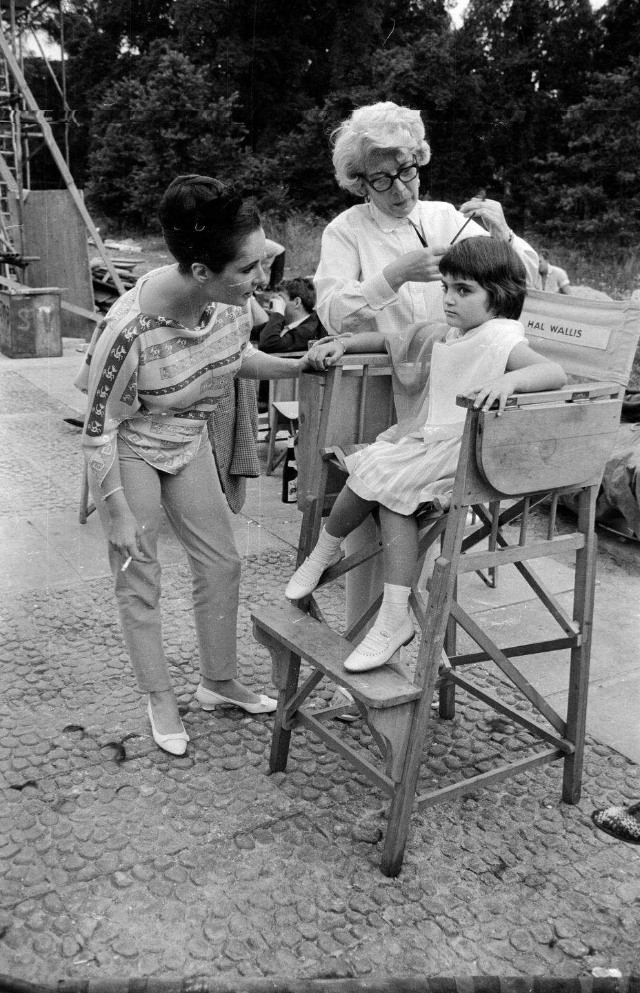 <p>While on the set of her mother Elizabeth Taylor's film <em>Becket, </em>Liza Todd gets her hair cut and styled by the film's hairdresser. We were getting our hair cut by our mothers over the bathroom sink at that age ...</p>